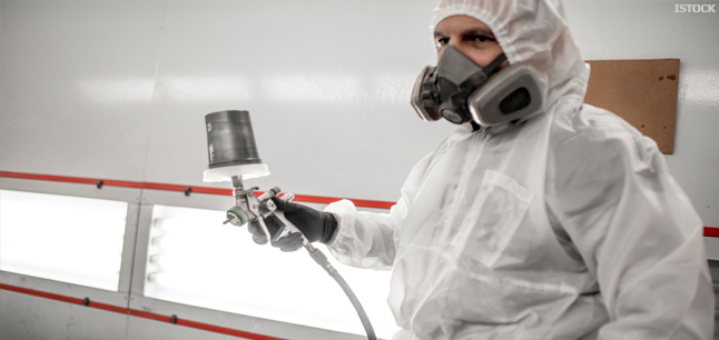 Car paint sprayer in coveralls and a breathing mask holding a paint spray gun