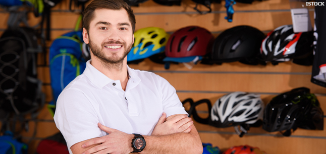 Shop worker standing in front of cycle helmet display in bike shop