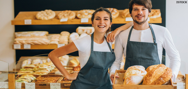 Two bakers holding fresh loaves in a bakery shop