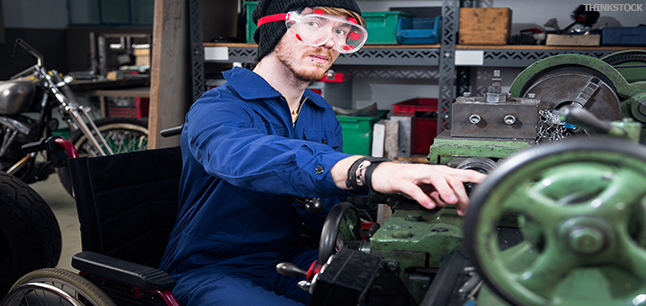 Mechanic in wheelchair wearing safety goggles, working on turning lathe