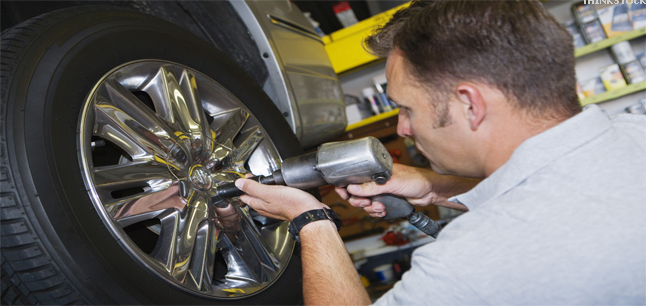 A mechanic fixing wheel nuts to a vehicle