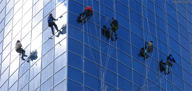 Workers washing windows of tall office building