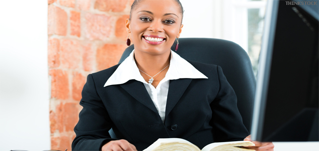 Young female lawyer working in her office and reading a law book