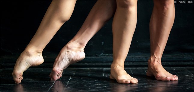 Ballerina's pointe on black wooden floor