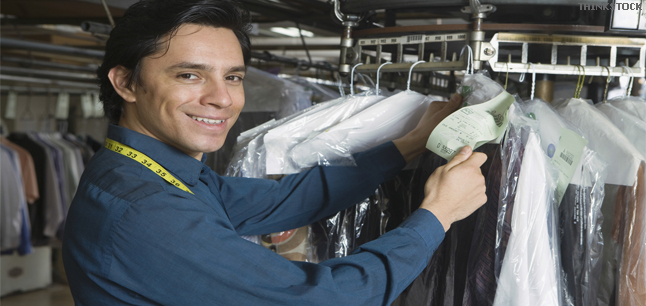 Young male laundrette owner sorting through clothes
