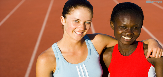 Sportswomen smiling with arms around each others shoulders