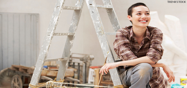 Smiling young female painter sitting on ladder