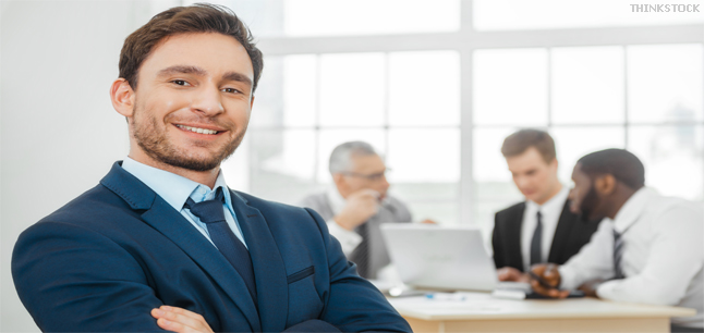 Businessman and his colleagues using laptop in background