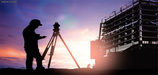 Survey engineer working in a building site at sunset